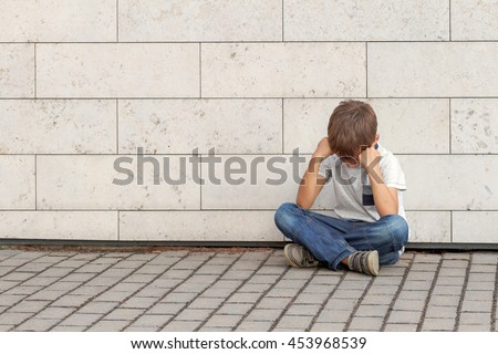 Sad, lonely, unhappy, disappointed child sitting alone on the ground. Boy holding his head, look down. Outdoor - stock photo