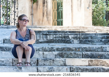 Sad lonely woman sitting on the steps - stock photo