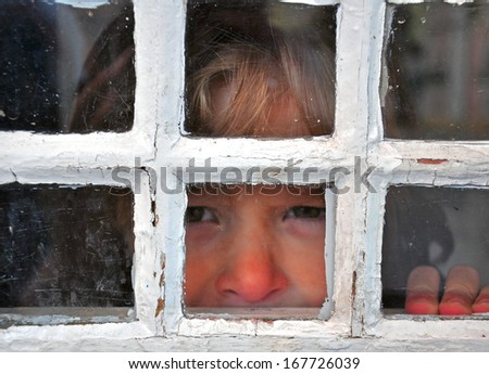 Sad look of the boy out of the window - stock photo