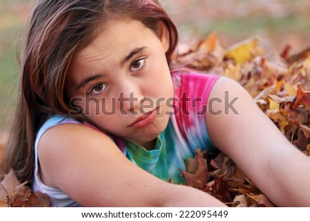 Sad looking eleven year old child sitting in leaves. - stock photo