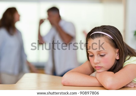 Sad looking girl with her fighting parents behind her