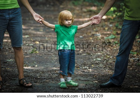 Sad looking girl with her parents - outdoor shot - stock photo