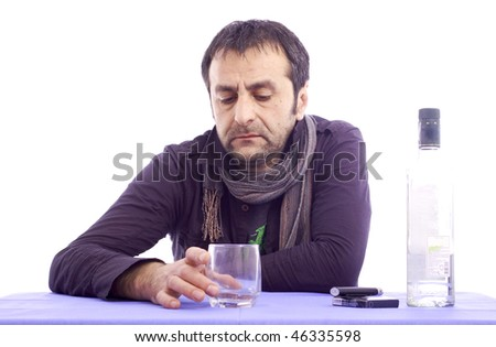 Sad looking man sitting at the table isolated over white background - stock photo
