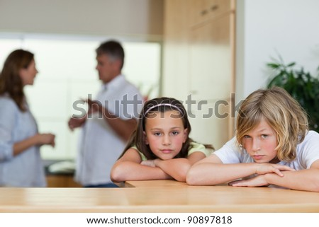 Sad looking siblings with their fighting parents behind them - stock photo