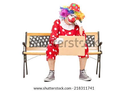 Sad male clown sitting on a wooden bench and holding a blank cardboard sign isolated on white background - stock photo