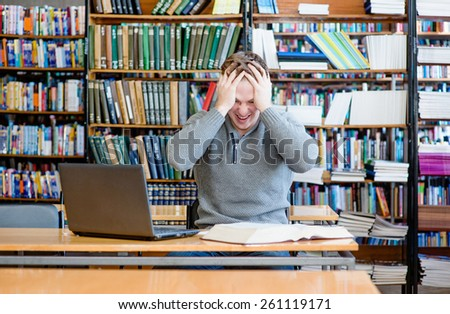 Sad male student in the university library - stock photo