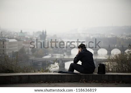 Sad man in autumn park, Prague - stock photo