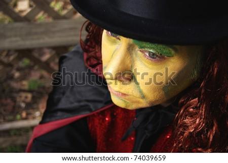 Sad man in green clown makeup - stock photo