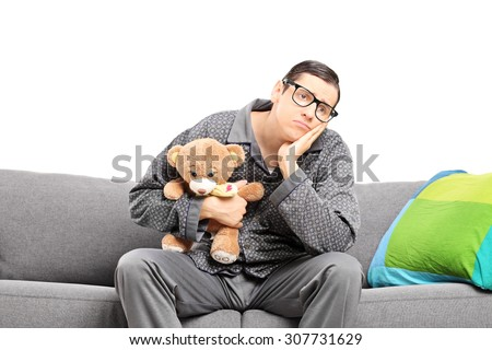 Sad man in pajamas holding a teddy bear seated on a sofa isolated on white - stock photo