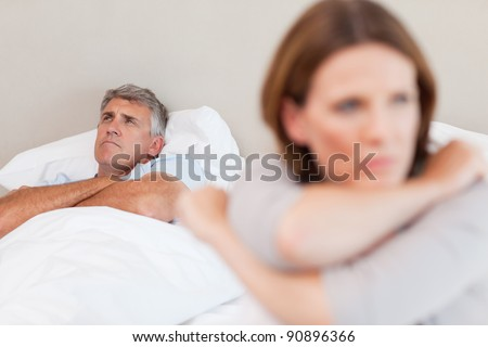 Sad man in the bed with his wife in the foreground