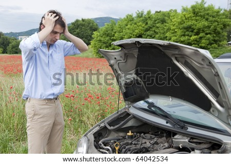 sad man looking at his broken car - stock photo