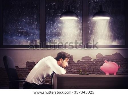 Sad man looks at his last savings - stock photo