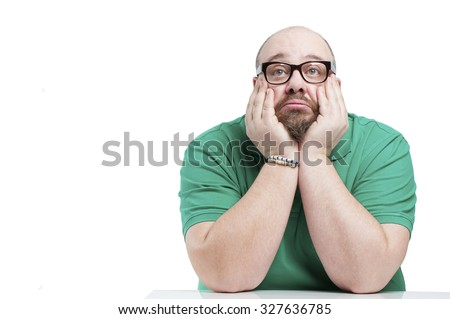 Sad man sitting at the table. Studio photography on a white background. - stock photo