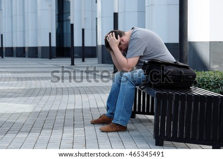 Sad man sitting in front of white office building