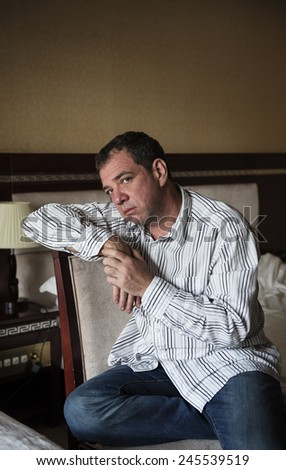 Sad man sitting on a chair in the hotel room  - stock photo