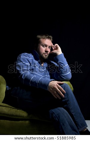 Sad Man Sitting on a Chair - Isolated Black Background