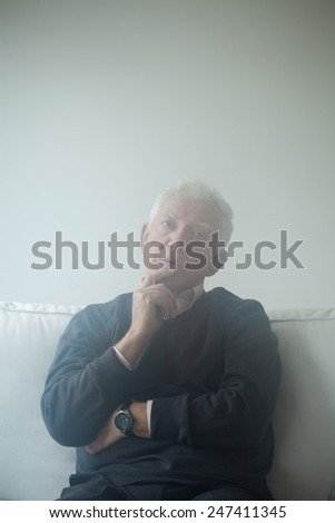 Sad man sitting on the sofa and thinking about problems - stock photo