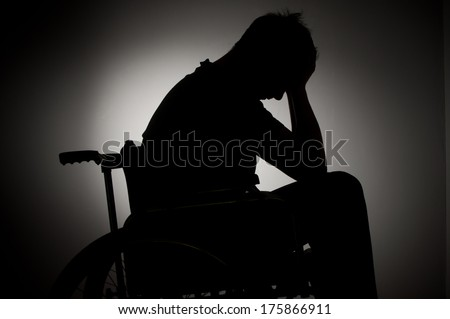 Sad man sitting on wheelchair in empty room - stock photo