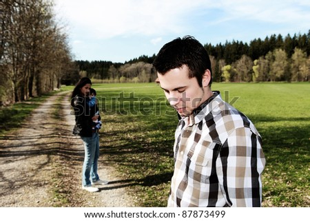 sad man standing aside from woman with baby, divorce - stock photo
