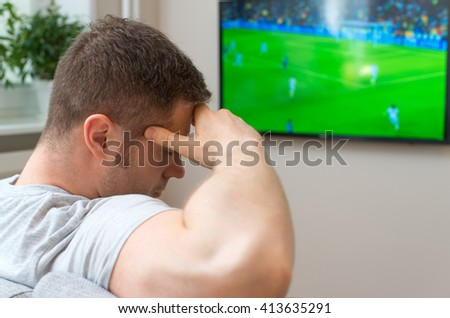 Sad man watching football match on television at home. - stock photo
