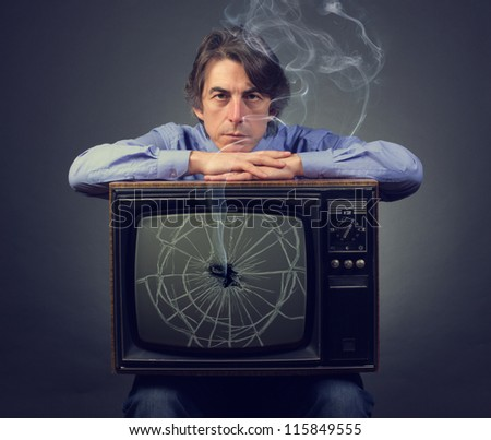 Sad man with a broken retro TV. - stock photo