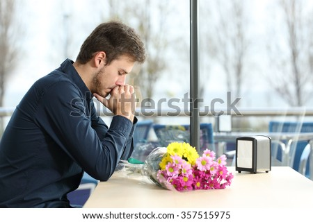 Sad man with bunch of flowers stood up in a date by his girlfriend in a coffee shop - stock photo