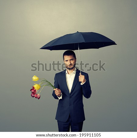 sad man with faded flowers standing under umbrella over dark background - stock photo