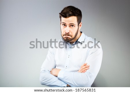 sad man with hands folded on grey background