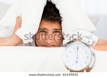 Sad man with head under the pillow waiting for his alarm clock to ring - stock photo
