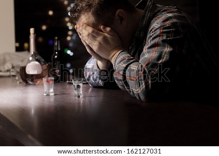 Sad man with problems sitting at the bar - stock photo