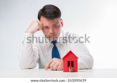 Sad Man with red paper house. Real estate concept on a white background