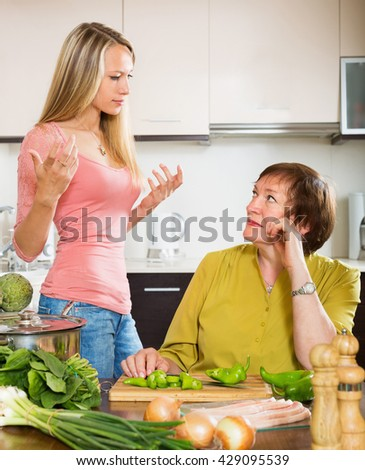Sad mature woman with angry adult daughter  sharing bad news in kitchen at home - stock photo