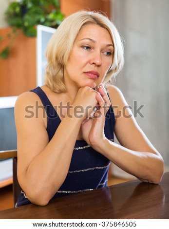 Sad middle-aged  woman sitting on table  in home - stock photo