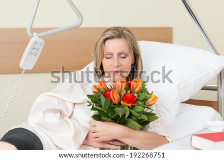 Sad middle-aged woman with downcast eyes clutching a bunch of roses to her chest as she lies in bed in hospital - stock photo