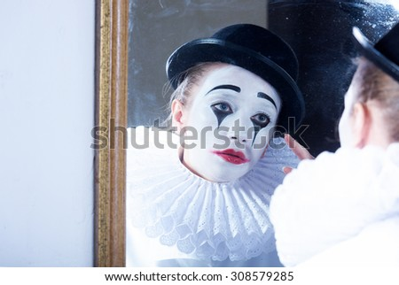 Sad mime Pierrot looking at the mirror - stock photo