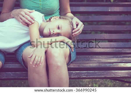 Sad mother and daughter sitting on bench in the park at the day time. - stock photo