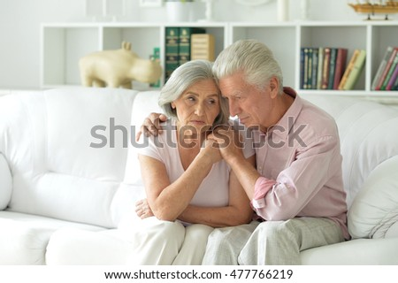 Sad nice elderly couple together at home