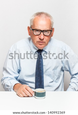 Sad old businessman with coffee