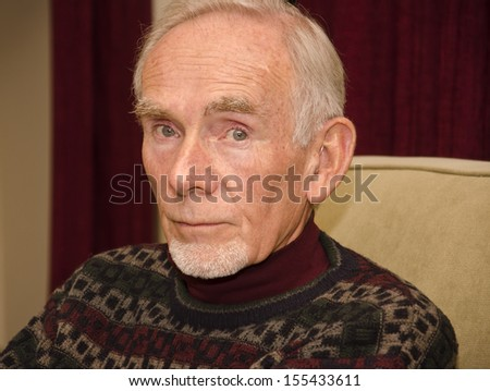 Sad old man staring straight ahead - stock photo