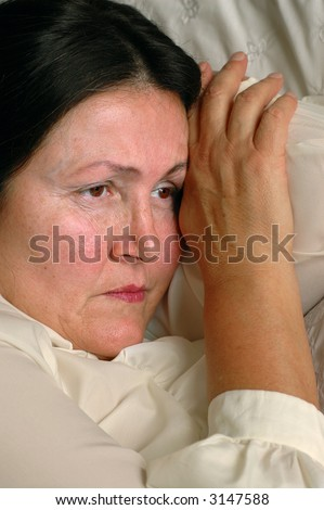Sad older woman lying on bed, unhappy - stock photo