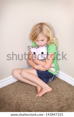 sad or lonely child in corner hugging a toy or stuffed animal - stock photo