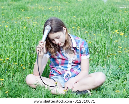 sad pensive teen girl with microphone in hand sits on a green lawn - stock photo