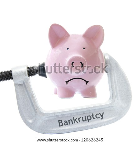 Sad piggy bank being squeezed in a Bankruptcy vice, on white - stock photo
