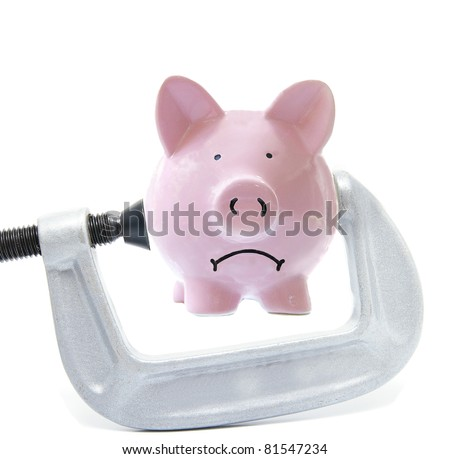 Sad piggy bank being squeezed in a vice, on white - stock photo