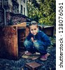 Sad poor child in the ruins of the city. - stock photo