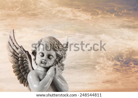 Sad praying angel on an orange heaven background for a condolence card. - stock photo
