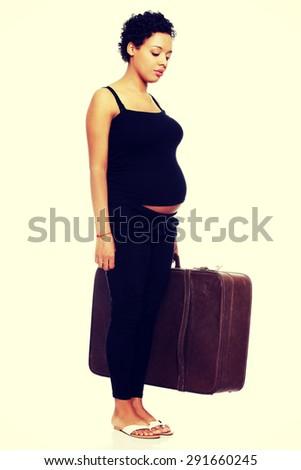 Sad pregnant woman with a lugagge - stock photo