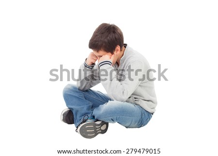 Sad preteen boy sitting on the floor isolated on a white background - stock photo