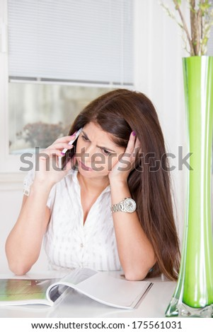 sad pretty girl in white shirt talking on the phone at home - stock photo