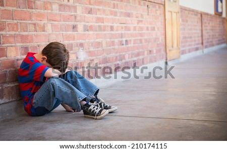 Sad pupil sitting alone in corridor at the elementary school - stock photo
